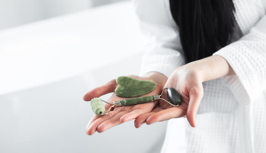 A woman holding a gua sha tool