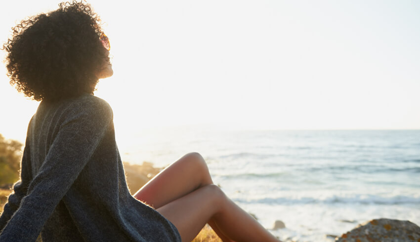 A woman sitting on a beach cliff